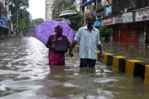 Old Couple walking in flooded Mumbai Road